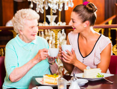 senior woman and her granddaughter drinking coffee